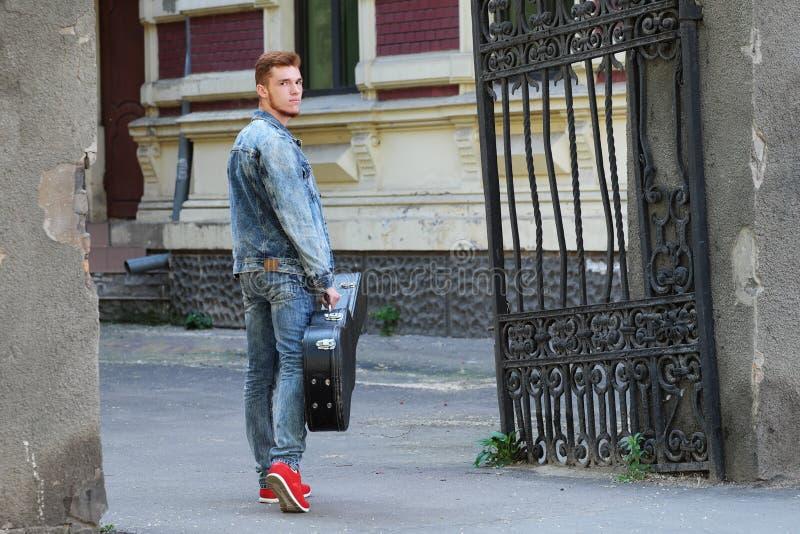 Молодой жизнерадостный парень с красными волосами на стробе с гитарой в случае стоковое изображение