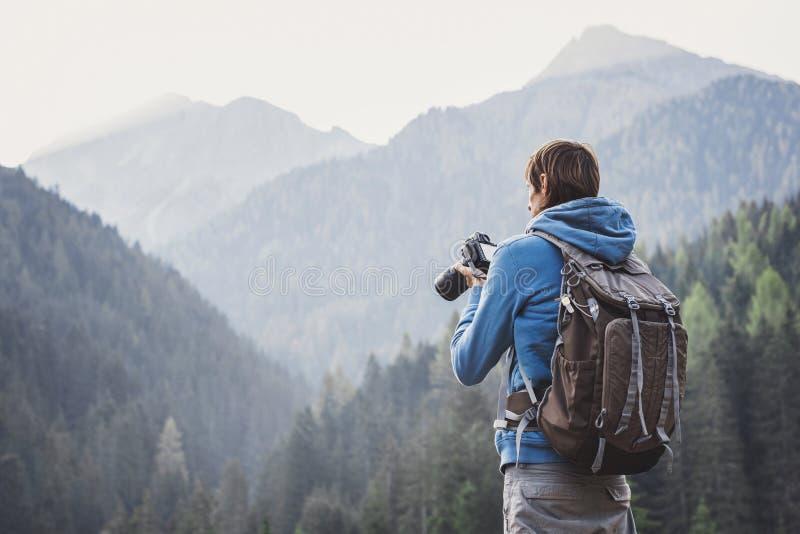 Молодой жизнерадостный фотограф человека принимая фотоснимки с цифровой фотокамерой в горах перемещение и активная концепция обра стоковая фотография