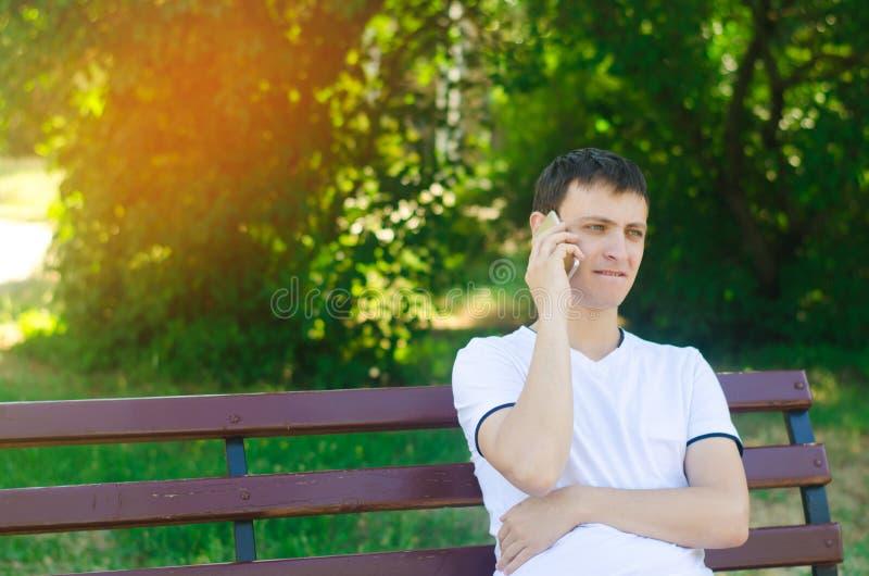 Молодой задумчивый европейский парень в белой футболке говорит на телефоне и сидит на стенде в парке города Концепция разрешать p стоковое изображение