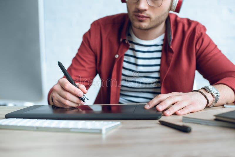 Молодой иллюстратор сидя таблицей стоковое фото
