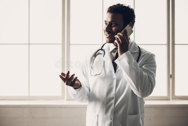 Молодой индийский доктор в белой форме с телефоном стоковое изображение