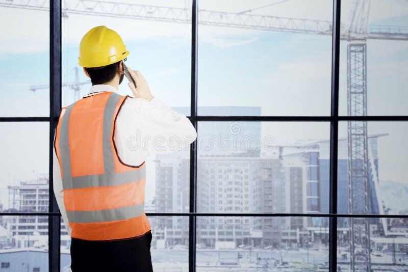Молодой инженер с smartphone в офисе стоковые фотографии rf