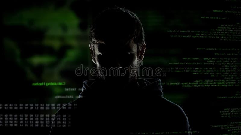 Молодой инкогнито человек, хакер интернета с номерами и код, угроза кибернетического преступления стоковые изображения rf