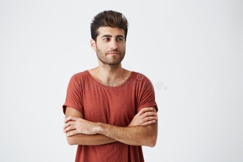 Молодой испанский битник нося красную футболку немножко усмехаясь, держащ руки пересеченный, и медитативный смотреть в сторону во стоковое фото