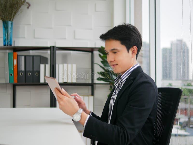 Молодой исполнительный азиатский человек сидит и усмехается на стуле и держать стоковая фотография