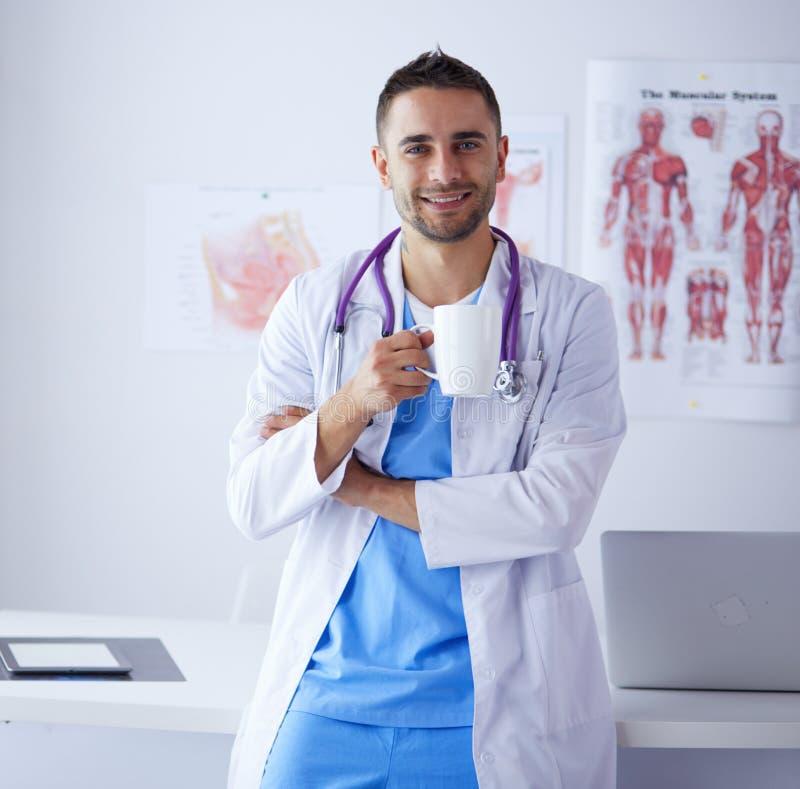 Молодой и уверенно мужской портрет доктора стоя в медицинском офисе стоковые изображения rf