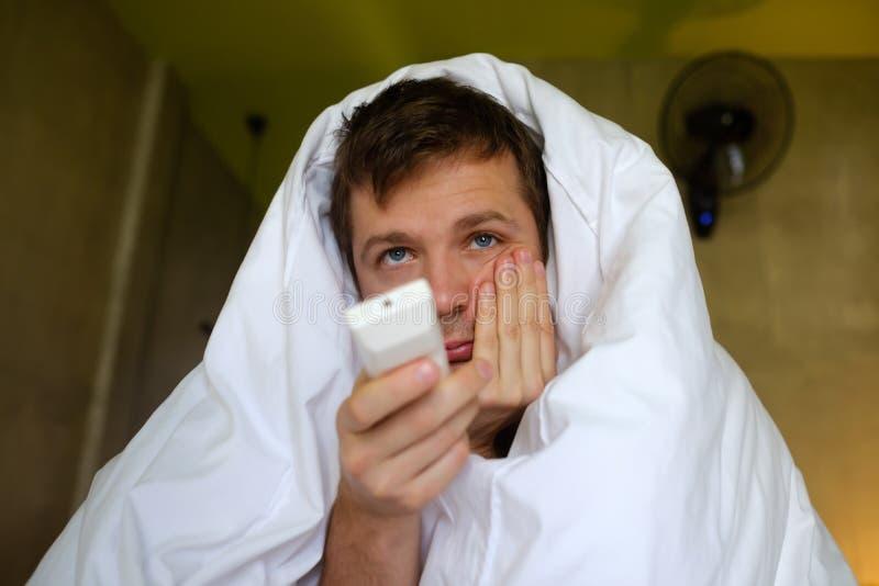 Молодой кавказец пробурил человека смотря ТВ сидеть дома живущая комната смотря утомлен стоковая фотография