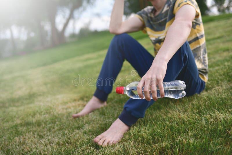 Молодой кавказский бегун человека ослабляя держащ бутылку питьевой воды и сидящ на траве в outdoors парка после спорта на предыду стоковое фото