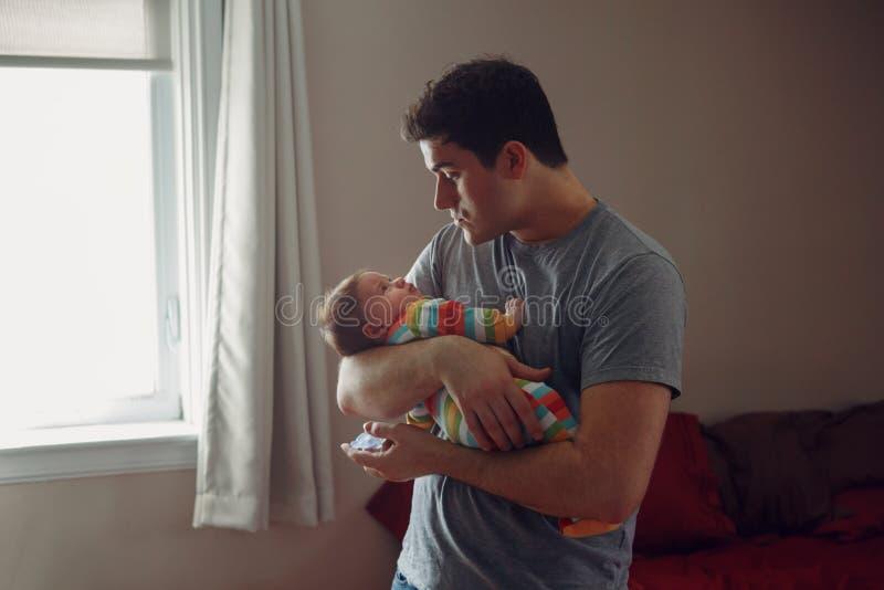 Молодой кавказский отец пробуя утихомирить вниз newborn младенца Мужской родитель человека держа тряся ребенка на его руках стоковое изображение