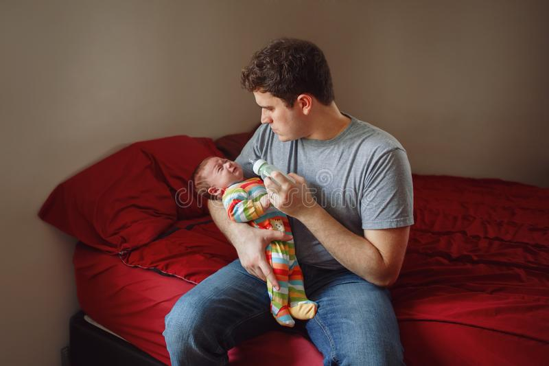 Молодой кавказский отец пробуя утихомирить вниз newborn младенца Мужской родитель человека держа тряся ребенка на его руках стоковое изображение rf