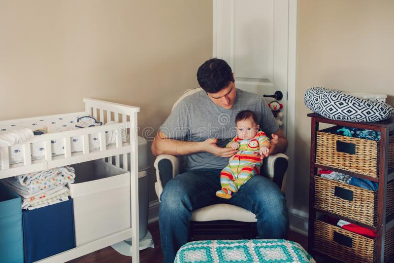 Молодой кавказский отец сидя в комнате питомника детей с newborn младенцем стоковые изображения rf