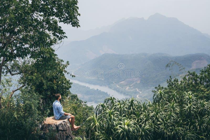 Молодой кавказский человек сидя на верхней части горы обозревая River Valley в деревне Nong Khiaw, Лаосе стоковые фото