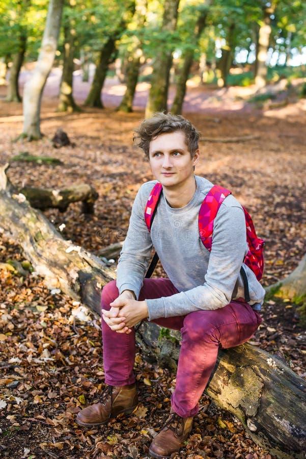Молодой кавказский человек с рюкзаком сидя и ослабляя на упаденном дереве в осеннем лесе смотря прочь усмехаться ванты вертикальн стоковые фото