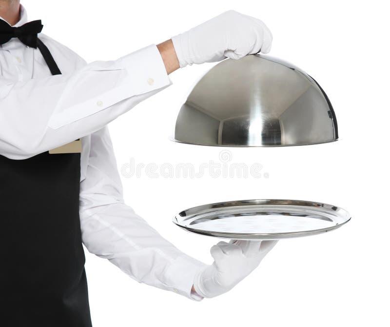 Молодой кельнер держа поднос металла с крышкой стоковое фото rf