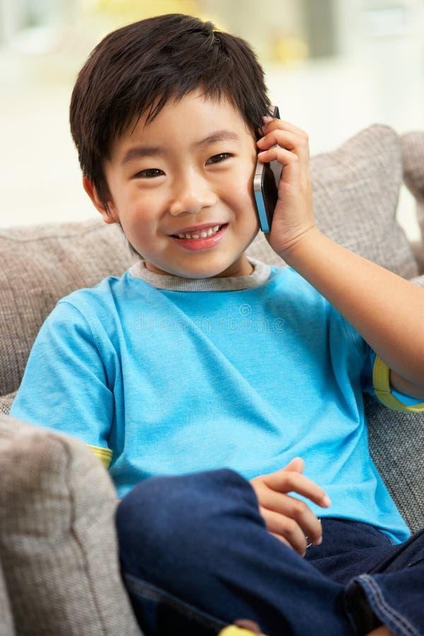 Молодой китайский мальчик используя мобильный телефон стоковые фото