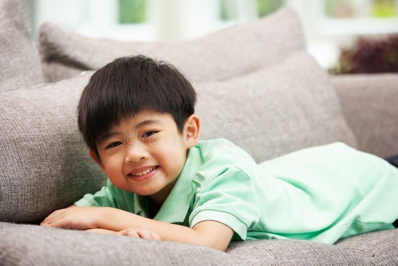 Молодой китайский мальчик ослабляя на софе дома стоковое изображение