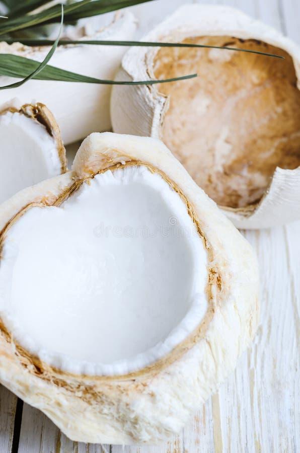 Молодой кокос на белой деревянной предпосылке стоковое фото