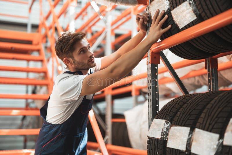 Молодой красавчик-механик, одетый в форму, работает в отделе автообслуживания, надевая шины на хранение стоковое фото rf