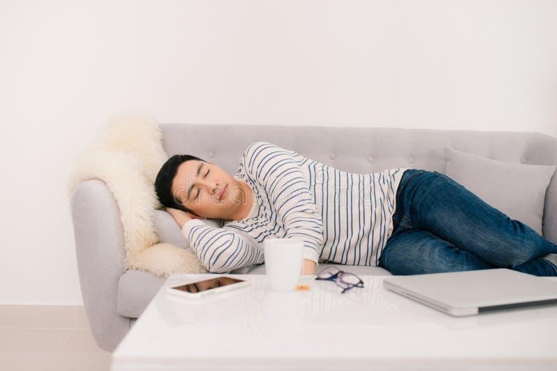 Молодой красивый азиатский человек спать на софе стоковые изображения rf