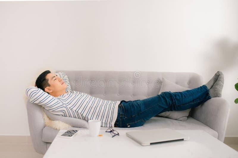 Молодой красивый азиатский человек спать на софе стоковое изображение rf