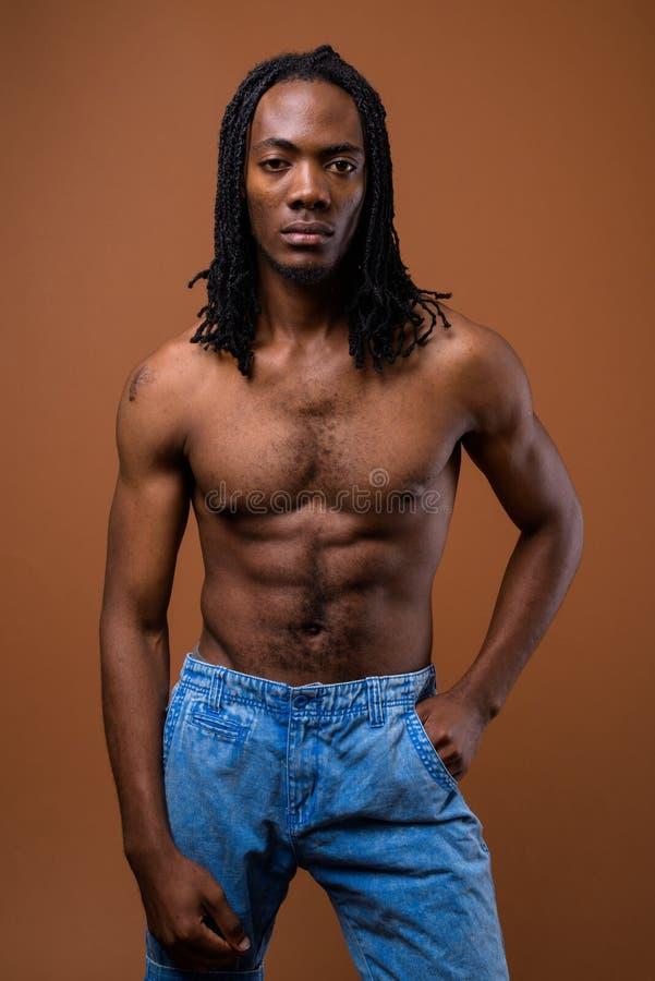 Молодой красивый африканский человек без рубашки против коричневой предпосылки стоковое фото rf