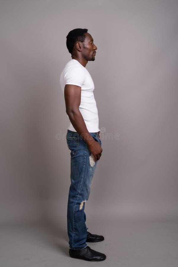 Молодой красивый африканский человек против серой предпосылки стоковое изображение