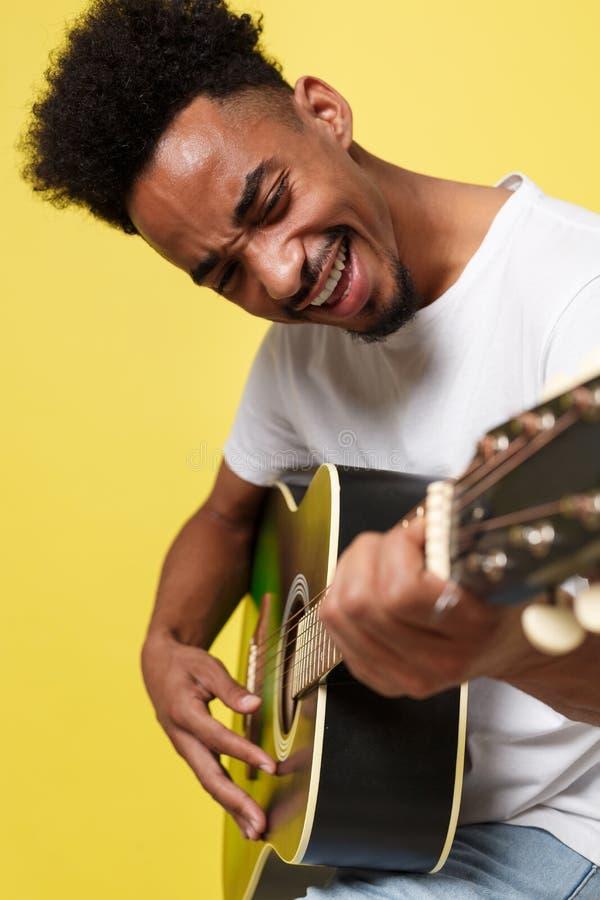 Молодой красивый Афро-американский ретро введенный в моду гитарист играя акустическую гитару изолированную на предпосылке желтого стоковая фотография