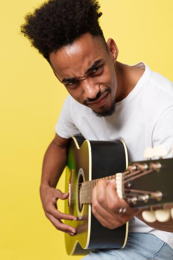Молодой красивый Афро-американский ретро введенный в моду гитарист играя акустическую гитару на предпосылке желтого золота стоковое изображение