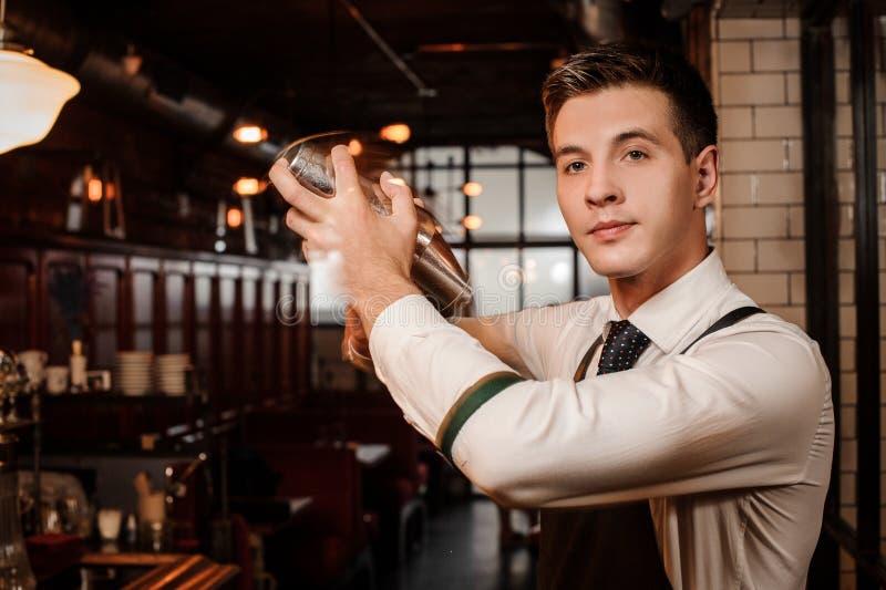 Молодой красивый бармен тряся свежее и вкусное cockta лета стоковые изображения