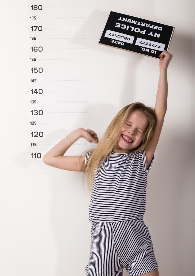 Молодой красивый белокурый ребенок со знаком, уголовные фотографии трудные дети, социальное напряжение стоковая фотография