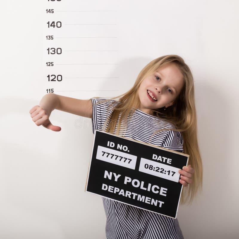 Молодой красивый белокурый ребенок со знаком, уголовные фотографии трудные дети, социальное напряжение стоковая фотография rf