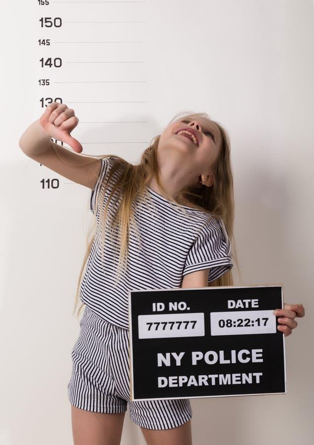Молодой красивый белокурый ребенок со знаком, уголовные фотографии трудные дети, социальное напряжение стоковое изображение