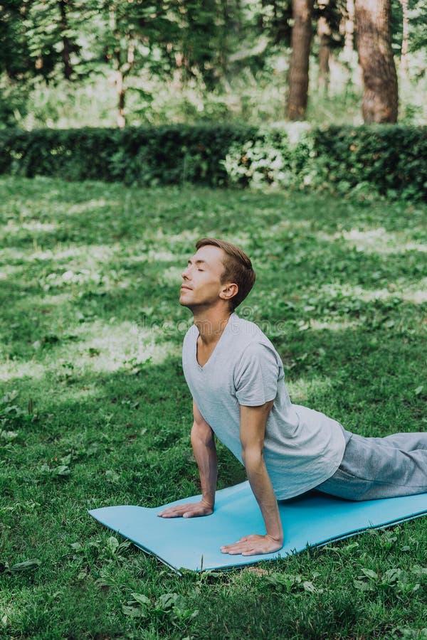 Молодой красивый белый человек в sportswear делает протягивать в парке на зеленой траве стоковая фотография