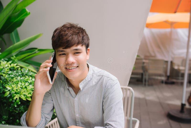 Молодой красивый бизнесмен звоня телефонный звонок в кафе внутри помещения стоковое изображение rf