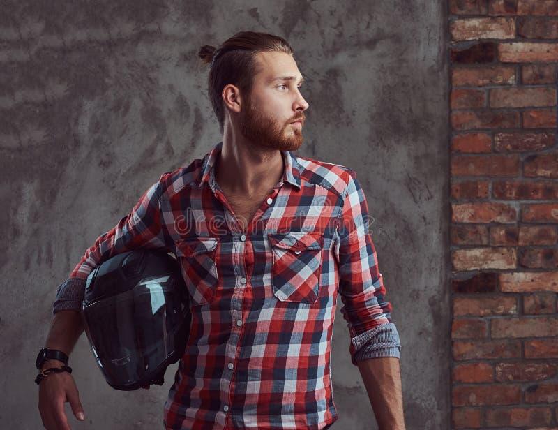 Молодой красивый велосипедист в рубашке фланели, шлем redhead мотоцикла владениями, представляя на серой предпосылке стоковые фото