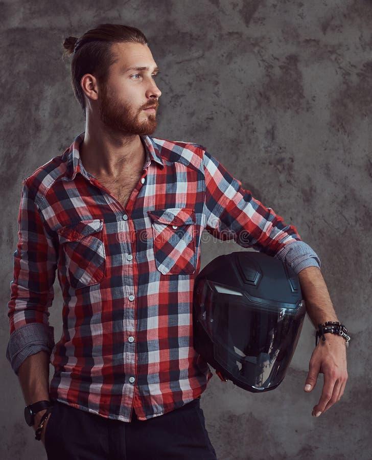 Молодой красивый велосипедист в рубашке фланели, шлем redhead мотоцикла владениями, представляя на серой предпосылке стоковое изображение rf