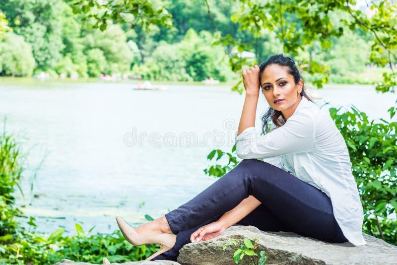 Молодой красивый восточный индийский американский путешествовать женщины, ослабляя на центральном парке, Нью-Йорк стоковое фото