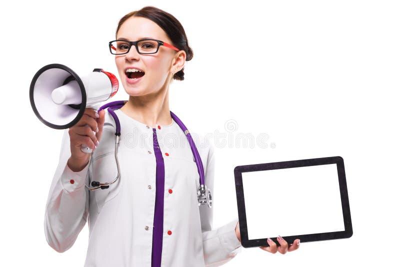 Молодой красивый женский доктор держа таблетку в ее руках говорит в мегафоне на белой предпосылке стоковые изображения