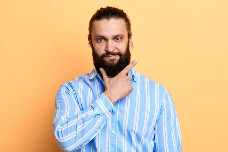 Молодой красивый жизнерадостный человек с ладонью на его бороде смотря камеру стоковое изображение rf