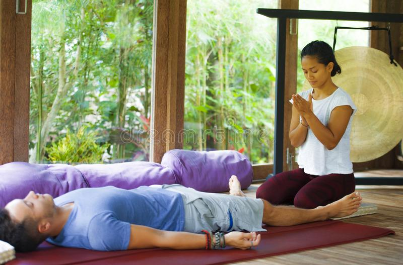 Молодой красивый и экзотический азиатский балийский терапевт здоровья давая телу тайский массаж привлекательному кавказскому чело стоковые изображения