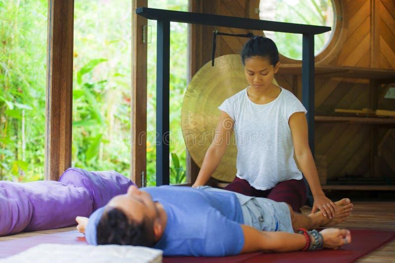 Молодой красивый и экзотический азиатский балийский терапевт здоровья давая телу тайский массаж привлекательному кавказскому чело стоковые фото