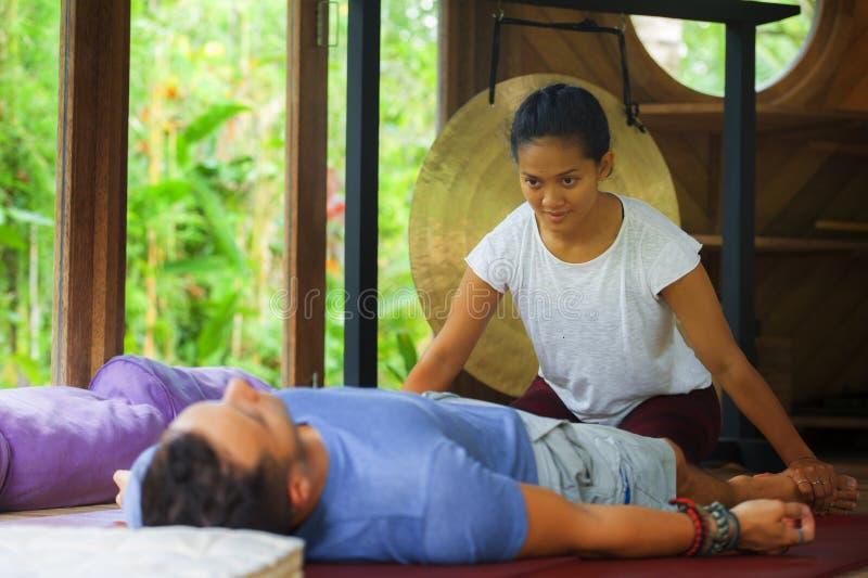 Молодой красивый и экзотический азиатский балийский терапевт здоровья давая телу тайский массаж привлекательному кавказскому чело стоковая фотография