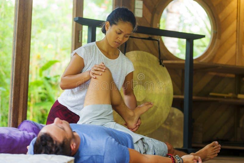 Молодой красивый и экзотический азиатский балийский терапевт здоровья давая телу тайский массаж привлекательному кавказскому чело стоковое фото