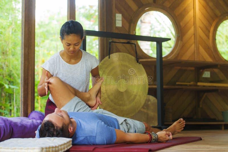 Молодой красивый и экзотический азиатский балийский терапевт здоровья давая телу тайский массаж привлекательному кавказскому чело стоковое фото rf