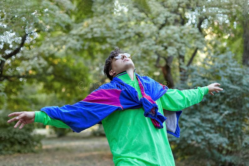 Молодой красивый кавказский человек с ярким причудливым стилем sportswear 70s стоит на парке утра Ручка в рте, золотые стекла, стоковые фото