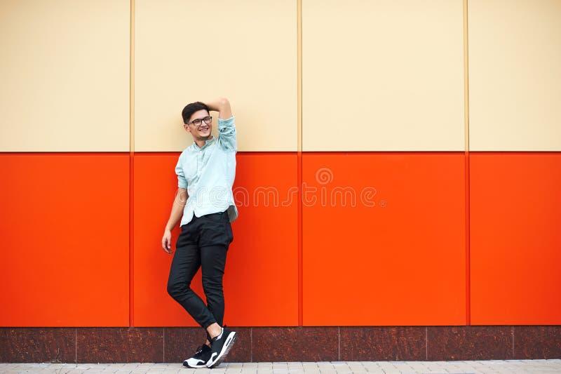 Молодой красивый мальчик в голубой рубашке, солнечных очках, стоя рядом с оранжевой предпосылкой стены стоковое фото rf