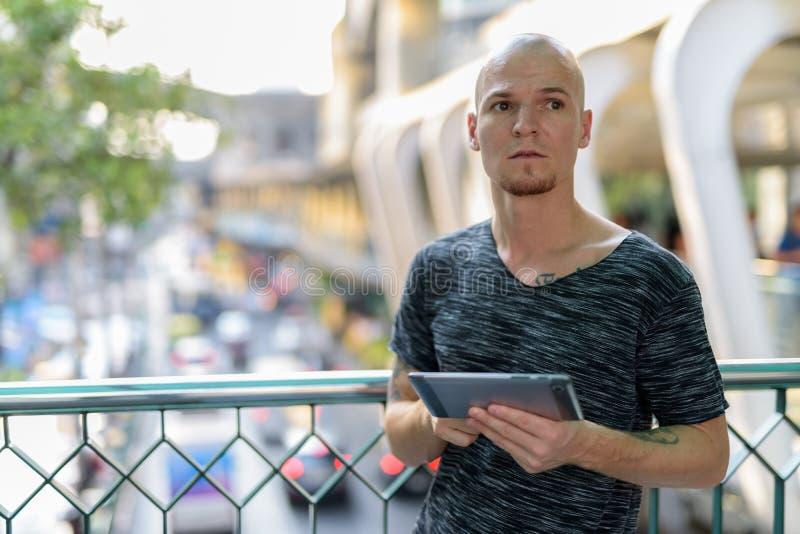 Молодой красивый облыселый человек думая пока держащ цифровую таблетку дальше стоковые фото