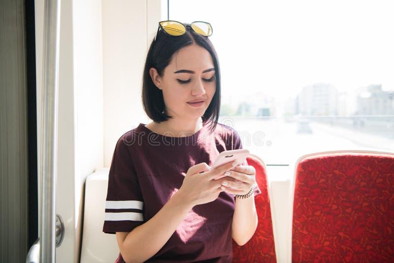 Молодой, красивый пассажир девушки в moving шине используя социальную сеть на ее smartphone и смотреть экран стоковые изображения