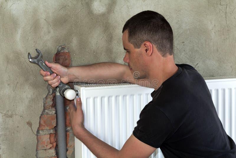 Молодой красивый профессиональный работник водопроводчика устанавливая радиатор топления на кирпичную стену используя ключ в пуст стоковое фото