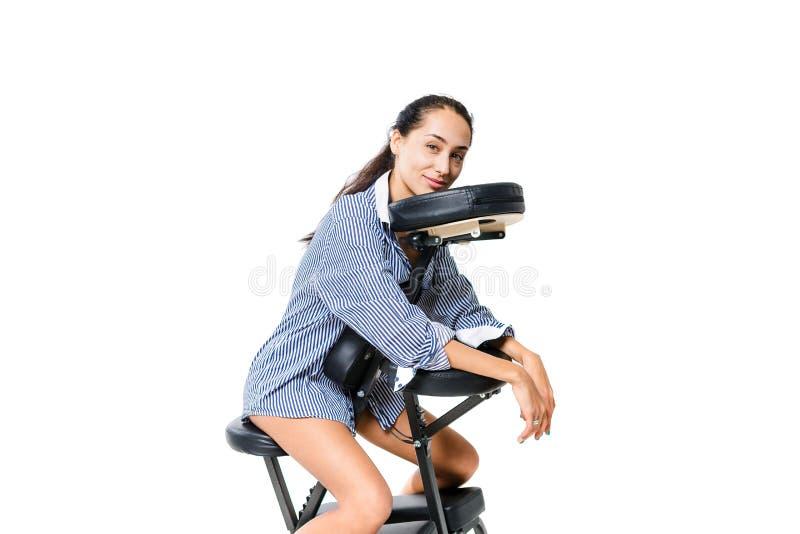 Молодой красивый работник офиса брюнет девушки в рубашке и при чуть-чуть ноги сидя на стуле массажа Темные кожа и волосы brun стоковое фото rf